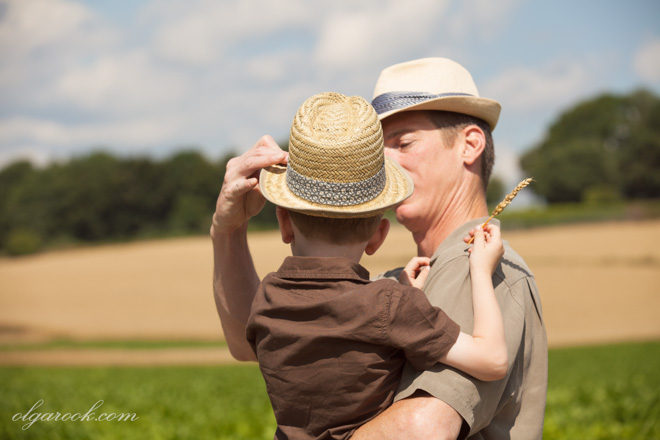 Photo of a father holding his young son in his arms. They both ware hats and are standing in front of a field. The boy is holding a wheat ear in his hand. This image awakens an idea of rural life and family traditions.