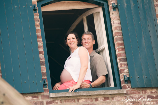 Photo of a pregnant woman and her husband in the window of their hous.