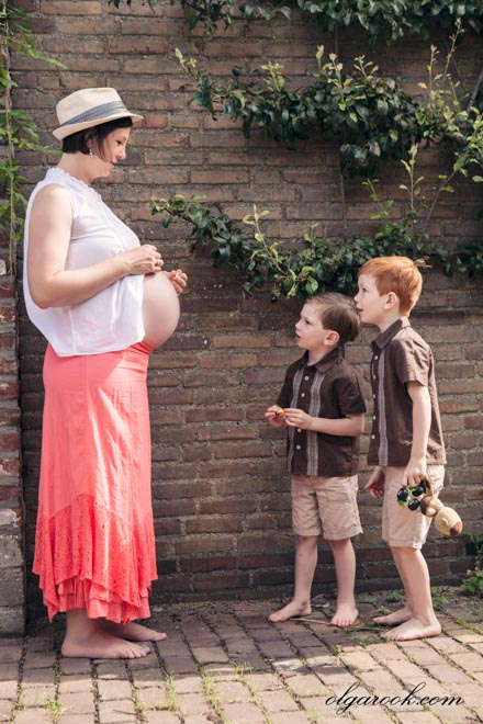 Two little boys are looking at their pregnant mother's belly wit awe.