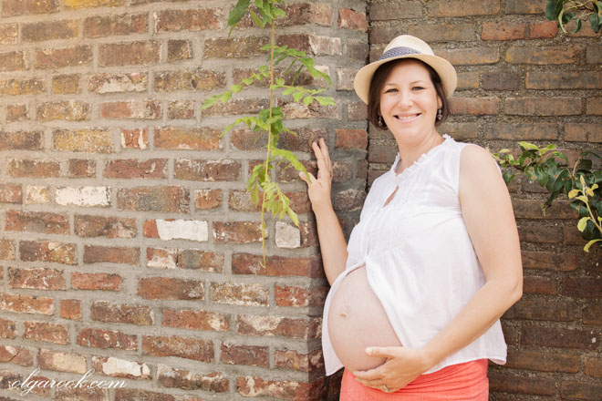 Pregnancy photo of a woman standing against a brick wall in her yard.