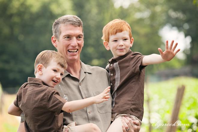 Foto van een vader, die zijn twee lachende zoontjes in zijn armen houdt.