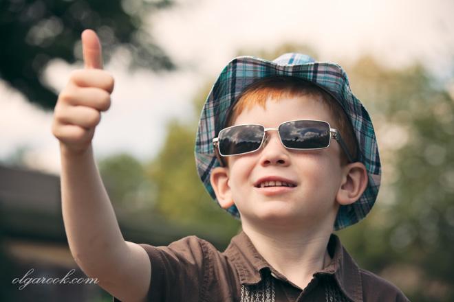 Portret van een roodharig jongentje met een hoedje en een zonnebril.