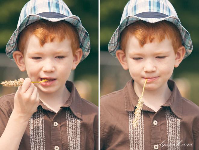 Portret van een klein roodharig jongentje met een aartje in zijn mond.