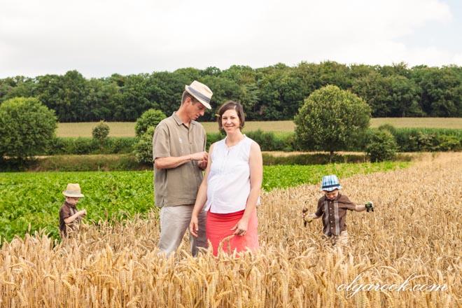 Foto van een gezin: vader, zwangere moeder en twee kleine jongens in een tarweveld.