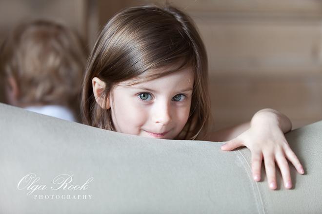 Portret van een klein meisje die van achter een bankje ondeugend kijkt.