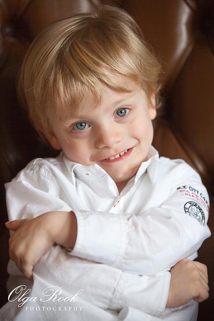 Foto van een klein blond jongenje, die op een grote antieke leunstoel zit.