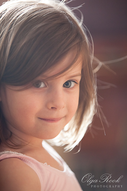 Portret van een klein meisje die tegelijk onschuldig en onduigend kijkt. Mooi zachte rozige tegenlicht.