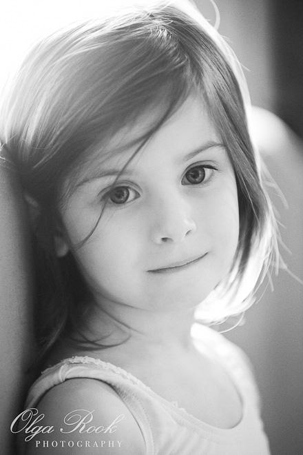 Zwartwit portret van een klein meisje, die dromerig kijkt.