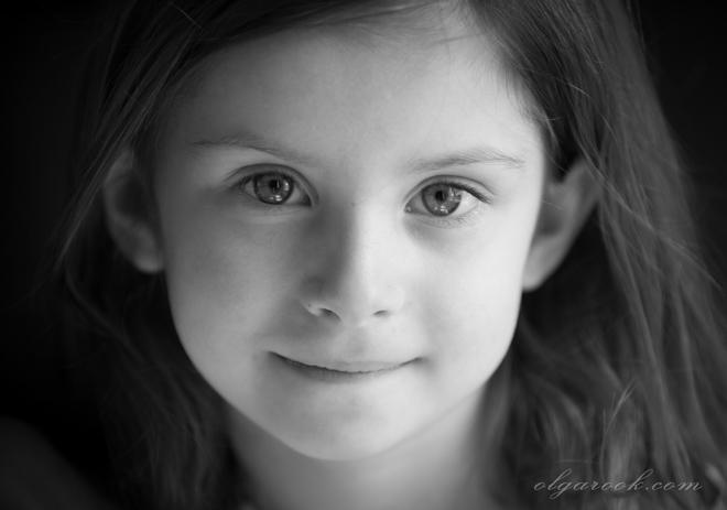 Portret van een klein meisje: haar ogen zijn intelligent en vol aandacht.