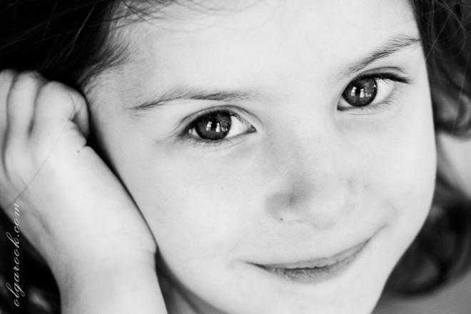 Zwart-witte foto van een klein meisje met grote stralende ogen.