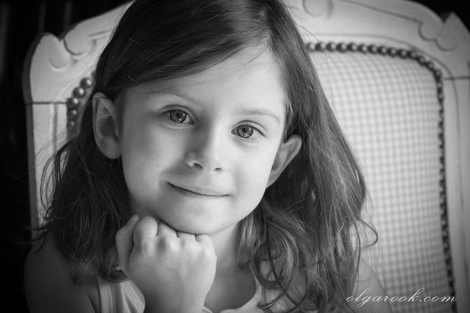Portret van een klein meisje op een stoel. Ze is heel jong maar haar glimlach toont veel zelfvertrouwen aan.