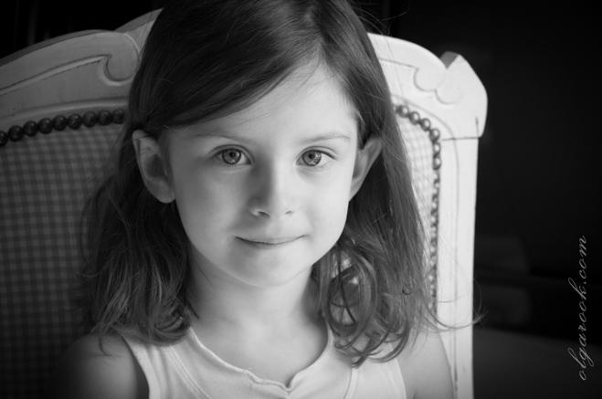 Portret van een klein meisje zittend op een stoel. Ze heeft een zacht glimlach.