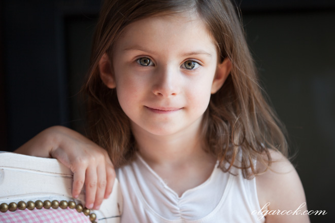 Klassieke portret van een klein meisje met een subtiel glimlach.