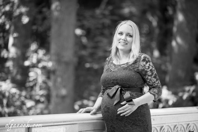 Foto van een chique geklede zwangere vrouw op een brug in een park.
