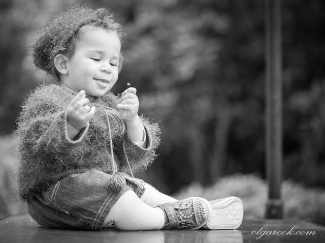 Zwart-wit portret van een eenjarig meisje met een klein bloemetje in haar hand.