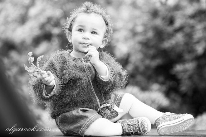 Zwart-witte portret van een klein meisje met een bladje in haar hand