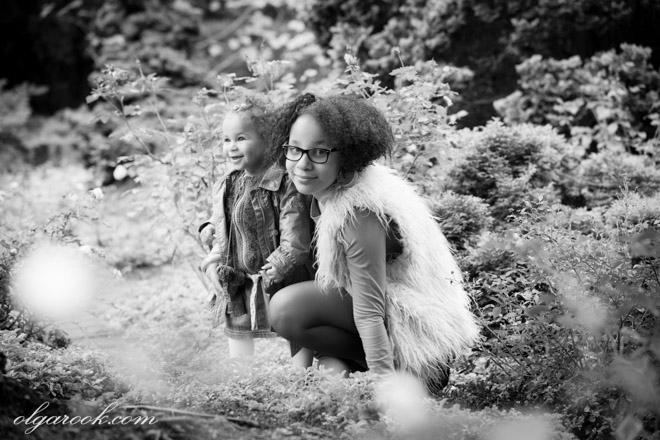 zwart-witte foto van zusjes van 1 en 10 jaar oud in een park