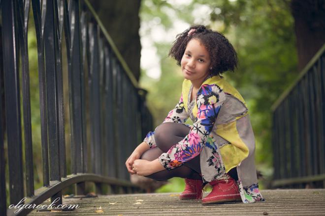 Romantische foto van een krullerig meisje om een brug in een park.