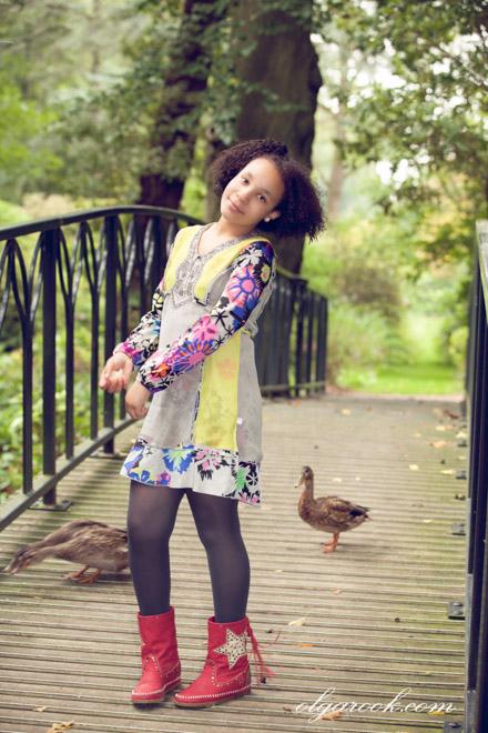 Kleurrijke foto van een meisje, die eenden voert in een park.