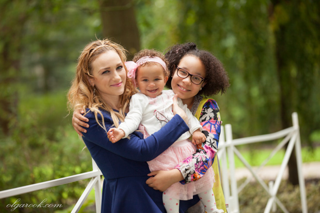 Foto van een moeder met twee dochters in een groene park.