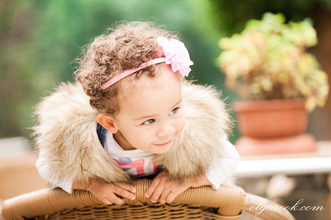 Portret van een klein krullerig meisje in pasteltinten.
