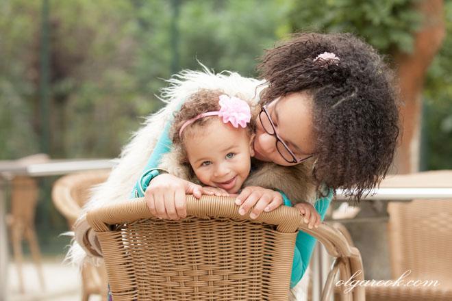 Foto van twee krullerige zusjes in een park: de oudere zus geeft een zoentje aan de kleinere.