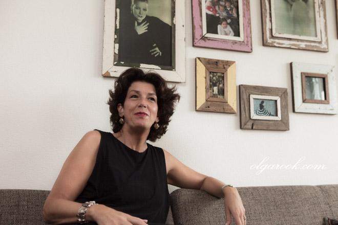 Nostalgische kleurenportret van een elegante vrouw tegen een muur met fotolijsten.