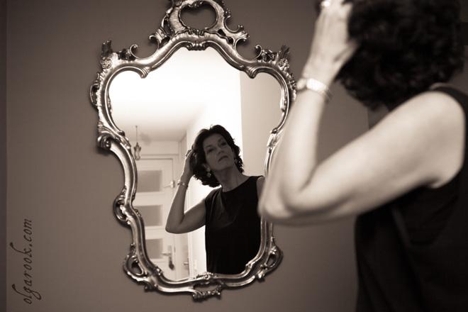 Sepia foto van een mooie vrouw die voor een baroque spiegel staat.