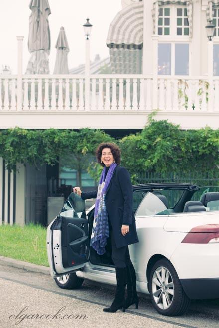 Kleurenfoto van een lachende elegante dame, die naast haar auto staat.