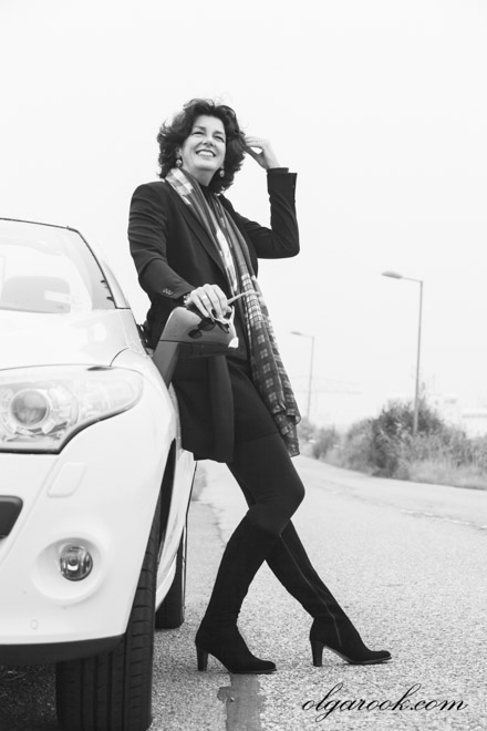 Zwart-wit portret van een mooie chique geklede dame die naast de weg voor haar auto staat.