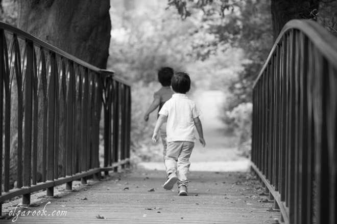 Black and white photograph of two little boys running across a bridge in a park.