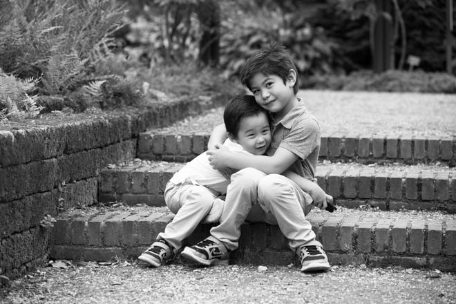 Photo of two little brothers sitting on the steps in a park, hugging.