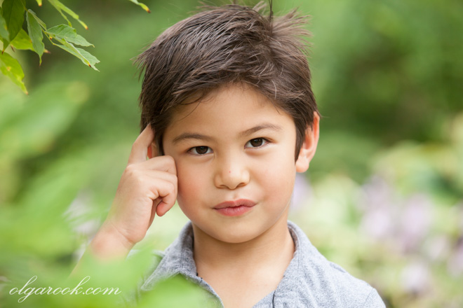 Color portrait of a boy in a park among the green leaves and flowers.