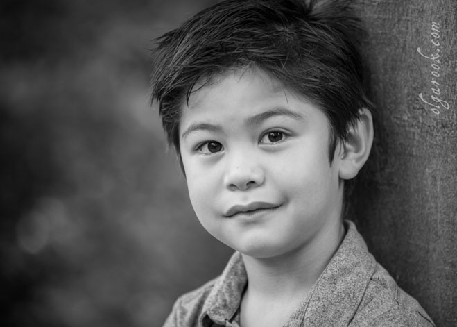 Black and white portrait of a boy with dark hair and bright dark eyes.
