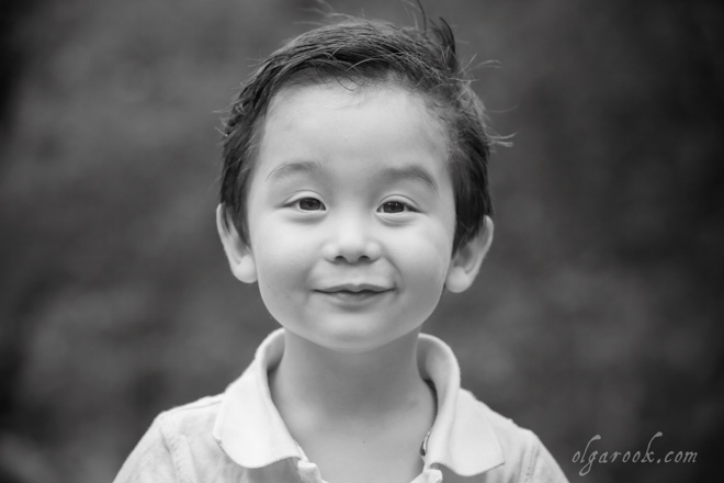 Zwart-wit portret van een klein jongetje met een ondeugend blik in zijn ogen.
