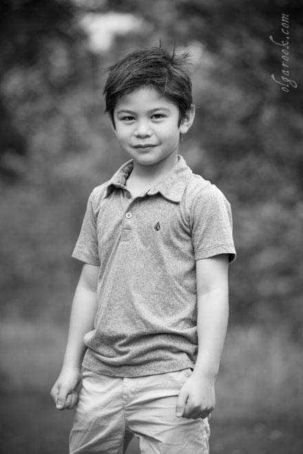 Foto van een zesjarige jongen in een park. Zijn houding is stoer en zelfverzekerd.