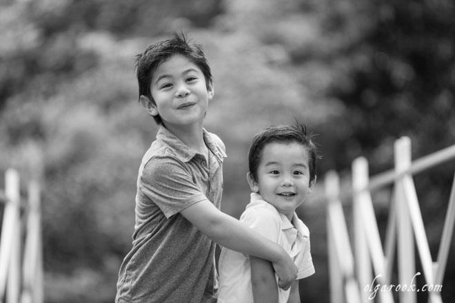 Zwart-wit foto van twee lachende broertjes in een park.
