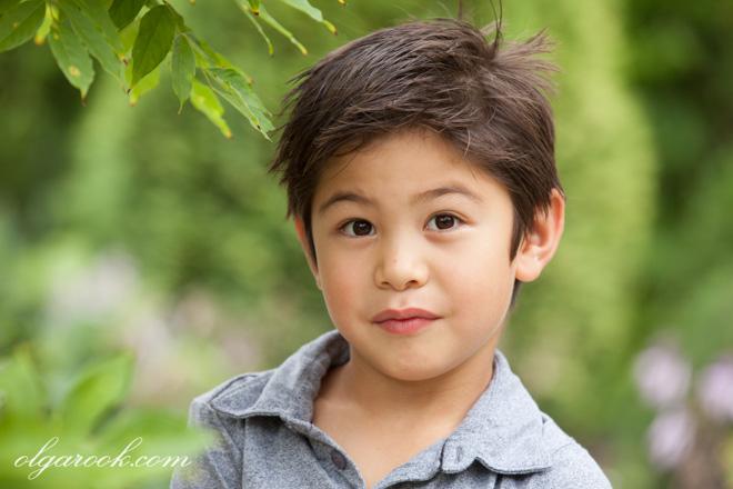 Portret van een zesjarige jongen tussen de bomen en bloemen in een park.