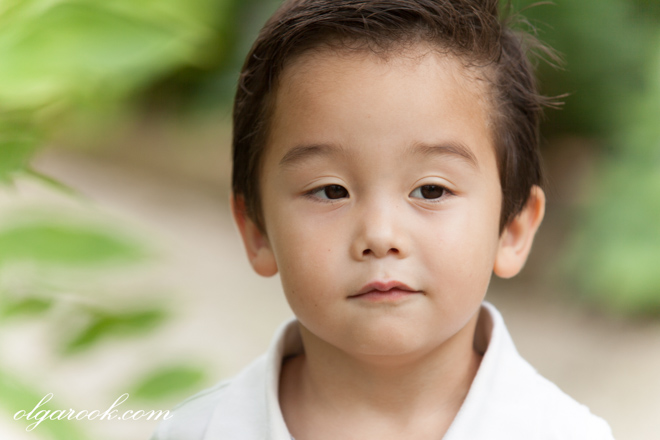 Kleurenportret van een kleine jongen in een park tussen de groene bladeren. De foto heeft het sfeer van puurheid en sereniteit.