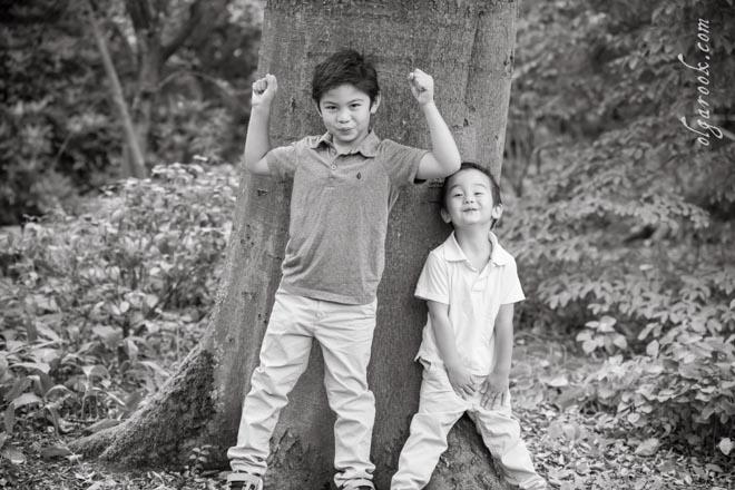 Foto van twee kleine broertjes in een park onder een grote boom.