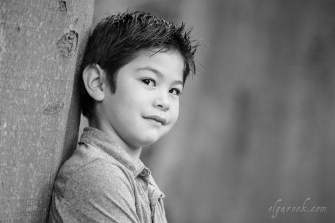 Zwart-wit portret van een jongen leunend tegen een boom in een park.