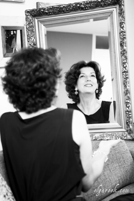 Black and white portrait of an elegant lady in front of a mirror.