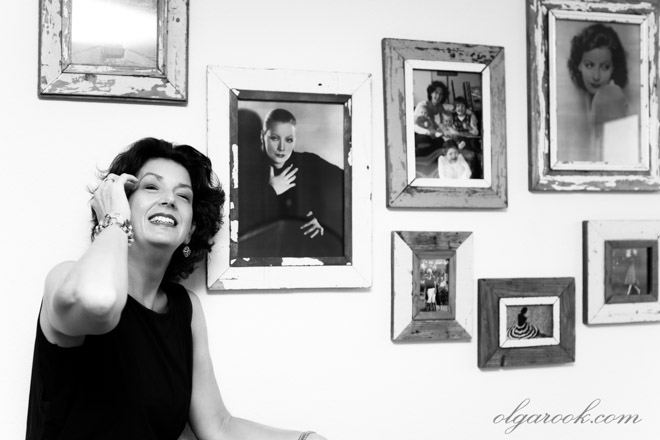 Black and white portrait of a lady next to a wall with photos of movie stars such as Greta Garbo and Audrey Hepburn.