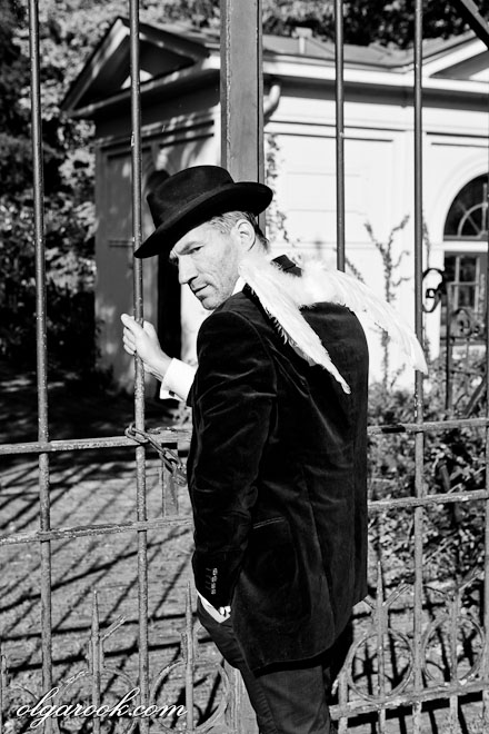 Black and white photo of ghost - he has wings but is also wearing a suit and a hat - in front of the closed cemetery gates.