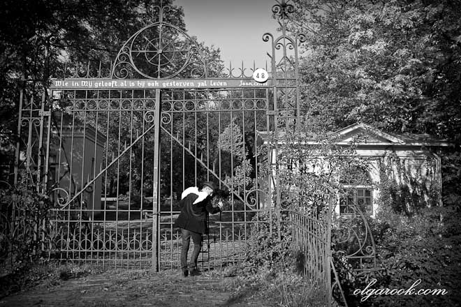 Photo of a ghost (a man with wings) standing outside a closed cemetery.