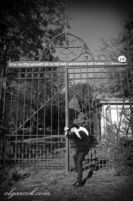 Photo of an old cemetery gates. A ghost (a man with angel wings) tries to open the closed gates.