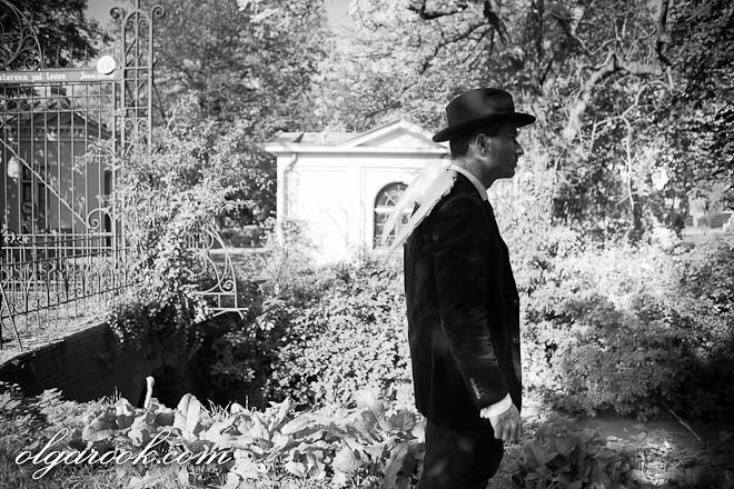 Antique style photo of a ghost (a man with wings and a hat) walking past an old graveyard.