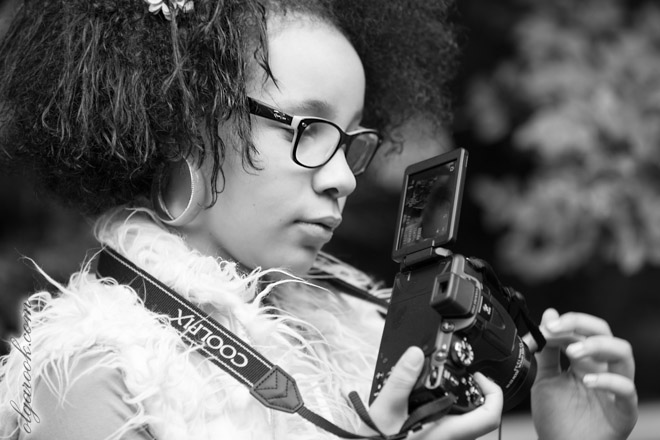 Black and white photo of a curly girl with a camera