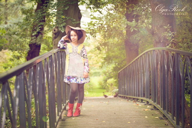 Romantic and dreamy child portraiture: photo of a girl wearing a hat and standing on a bridge in a park.