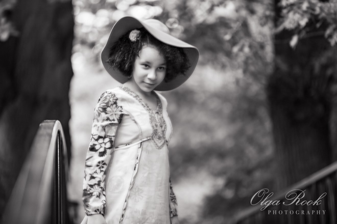 Antique looking black and white portrait of a girl in a park. She is wearing a hat and it reminds the fashion of the early twentieth century.